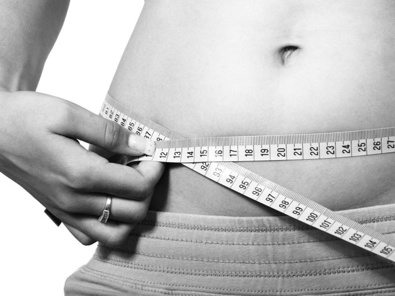 Black and white photo of woman measuring belly