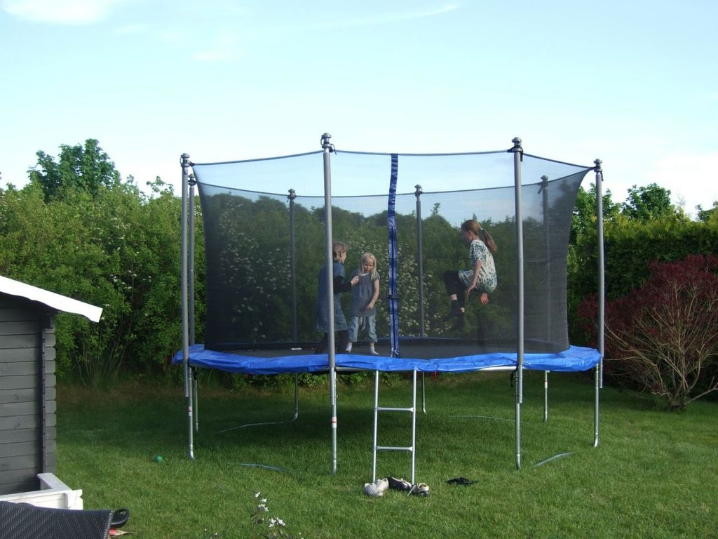 Children playing in trampoline with enclosure