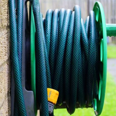 Green water hose on the side of a house