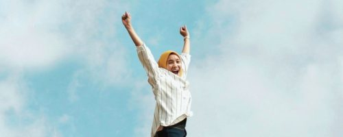 Woman jumping with arms up