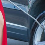 Woman pressure washing car in red evening dress