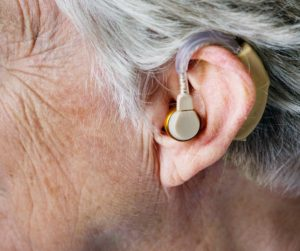 Elderly woman with hearing aid in ear