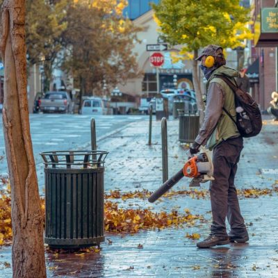 Man using leaf blower to clean sidewalk