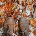 Boots surrounded by maple leaves on the ground