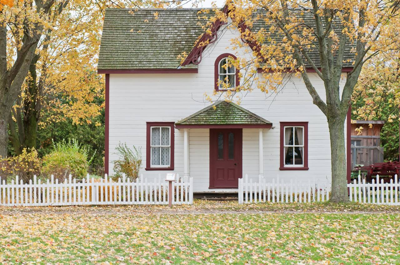 Small home with leaves in front yard