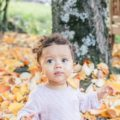 Baby sitting in leaves near bench