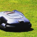 Automatic lawn mower on green grass
