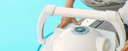 White robot pool cleaner with man picking up