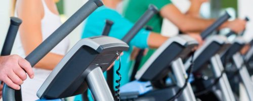 Group with senior people on elliptical trainer in gym