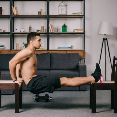 Working out triceps on chairs in apartment