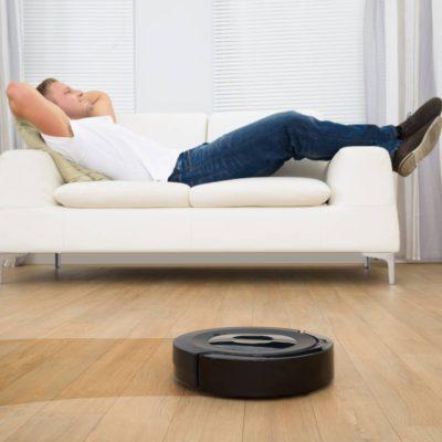 Man Relaxing On Sofa With Robotic Vacuum Cleaner On Hardwood Floor