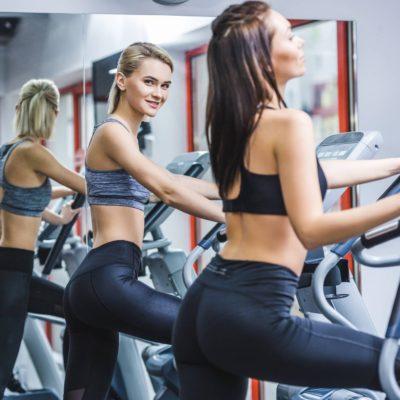 Women working out on an elliptical near mirror