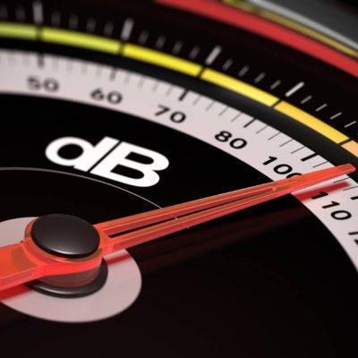 Decibel measurement. Gauge with green needle pointing 105 dB,