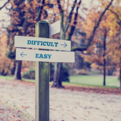 Signpost in a park or forested area with arrows pointing two opposite directions towards difficult and easy,