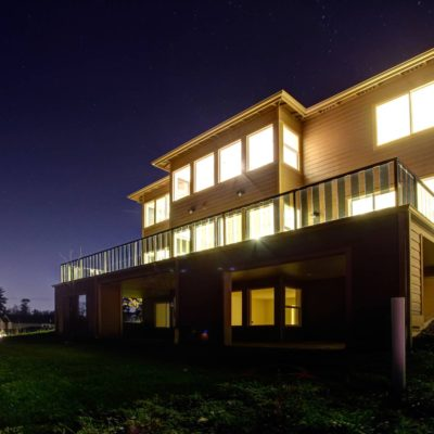 Big modern house with bright lights on in windows on a beautitul summer evening