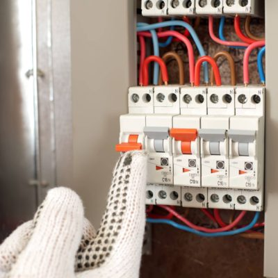 Electrician switching the power switch with protecting gloves.