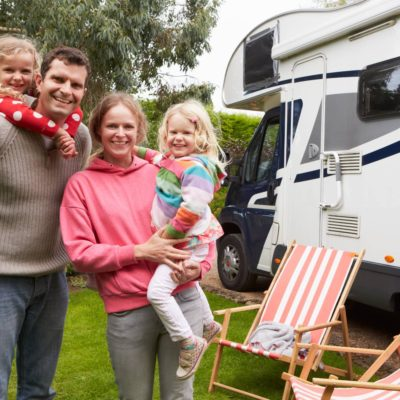 Portrait Of Family Enjoying Camping Holiday In Camper Van